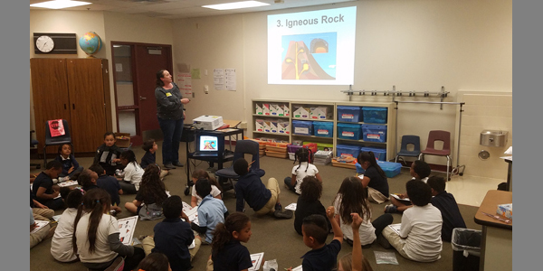 "Education and Outreach Specialist Rebecca Ely teaches 1st grade students about minerals' use in society and the concept of the ""rock cycle"", Jydstrup Elementary School, April 11th, 2019."